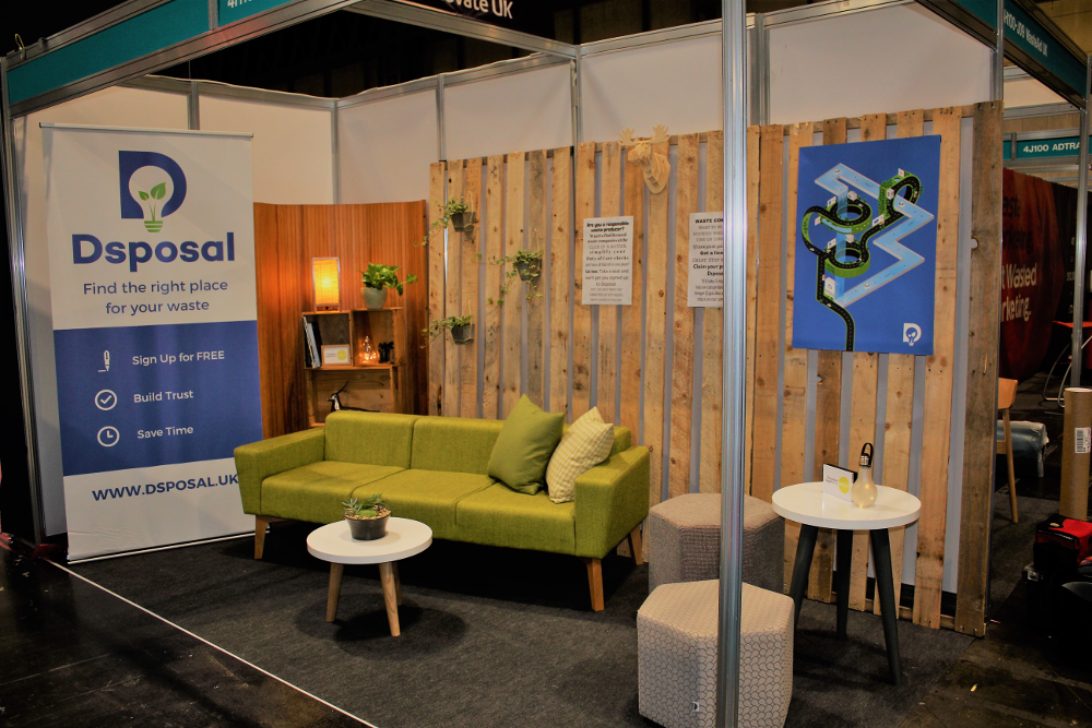 Photograph of Dsposal's lifestyle exhibitor stand at RWM 2018. Comfortable office furniture with wood paneling and Dsposal branding