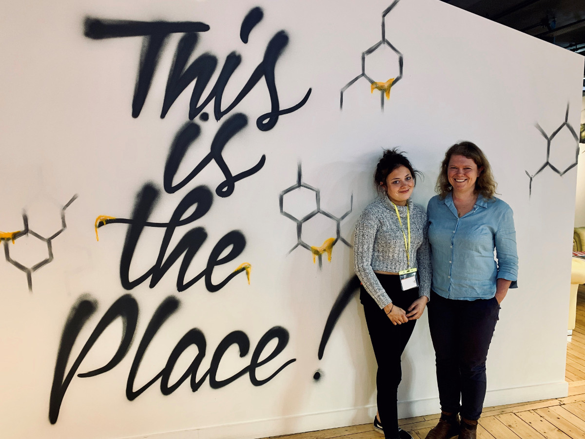 a girl, Cherry Passmore, and a woman, Sophie Walker, standing infront of a sign saying this is the place
