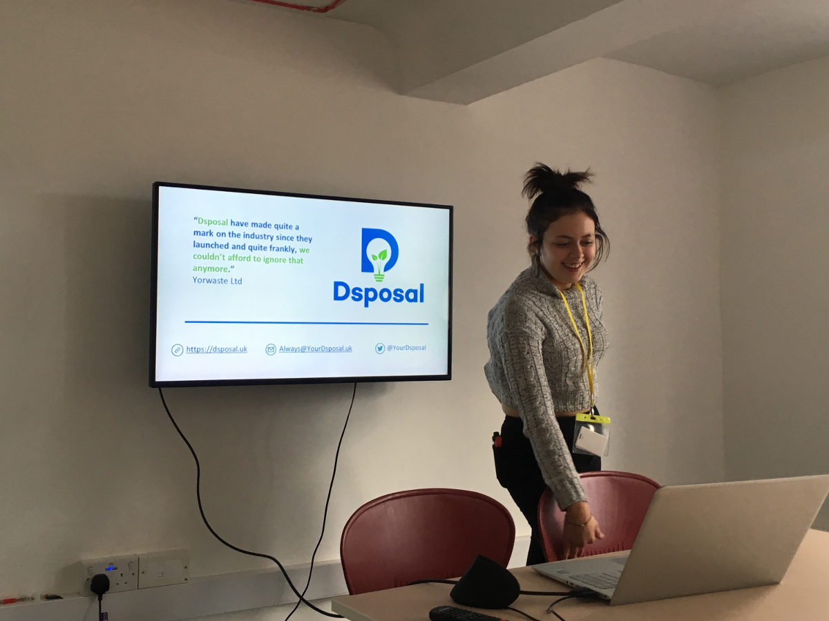 Girl, Cherry Passmore, giving a presenation in a small white room with Dsposal logo